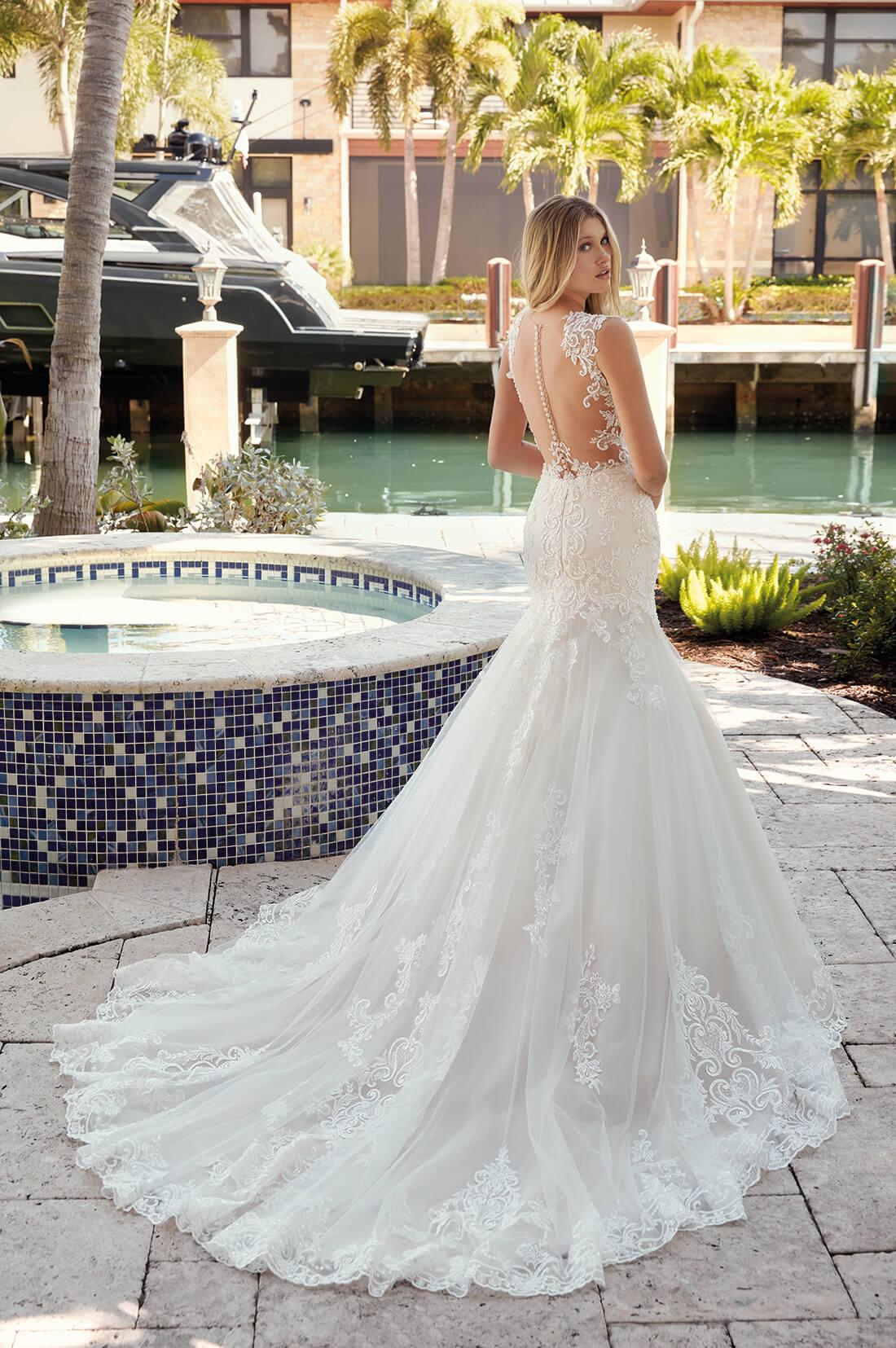 Blonde Braut in Brautkleid Meerjungfrau mit Knopfleiste und Träger in Tattoo Optik mit Wasser und Palmen im Hintergrund Rückenansicht mit Schulterblick