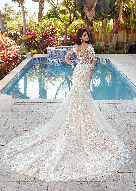 Schwarzhaarige Braut in Brautkleid Meerjungfrau langer Ärmel mit Tattoo Optik Rückenansicht vor einem Pool