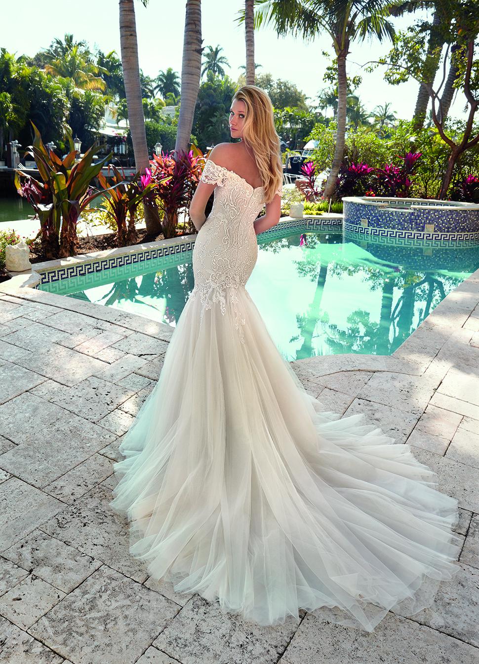 Blonde Braut in Brautkleid Meerjungfrau mit Carmen Träger vor einem Pool Rückenansicht mit Schulterblick