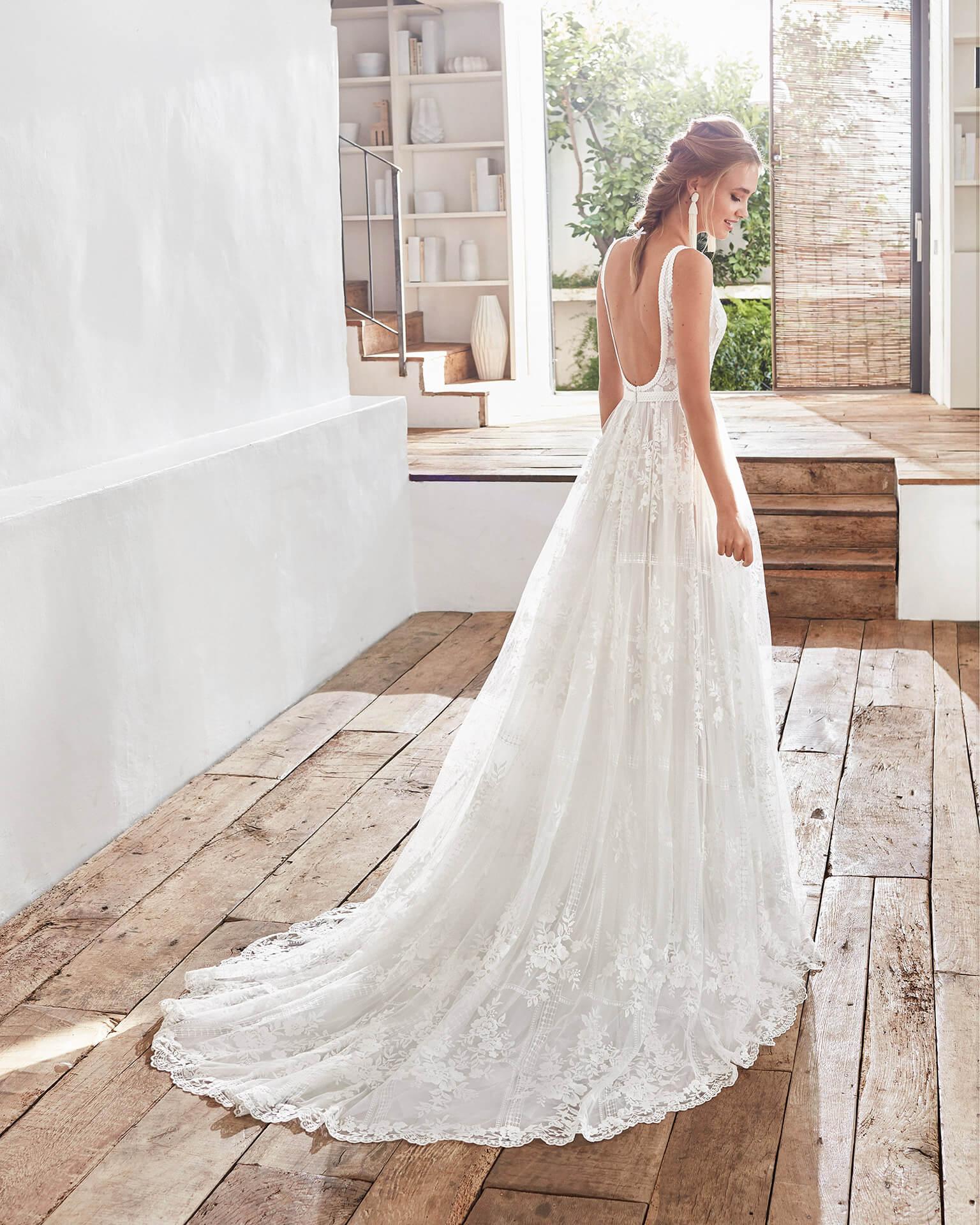 Blonde Braut in Brautkleid A-Linie Bohemian ärmellos in weißem Raum mit Holzboden und Fenster Rückenansicht