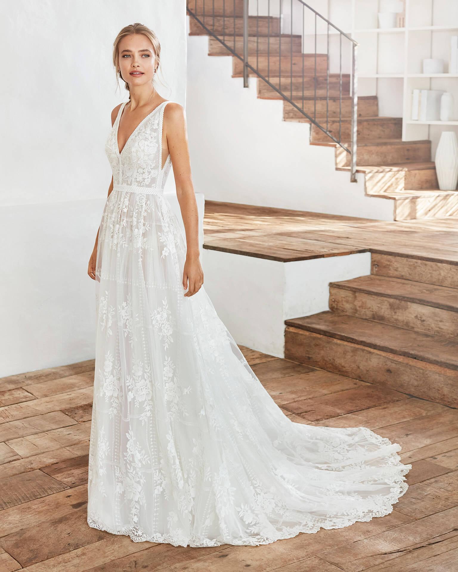 Blonde Braut in Brautkleid A-Linie Boho ärmellos in weißem Raum mit Holzboden
