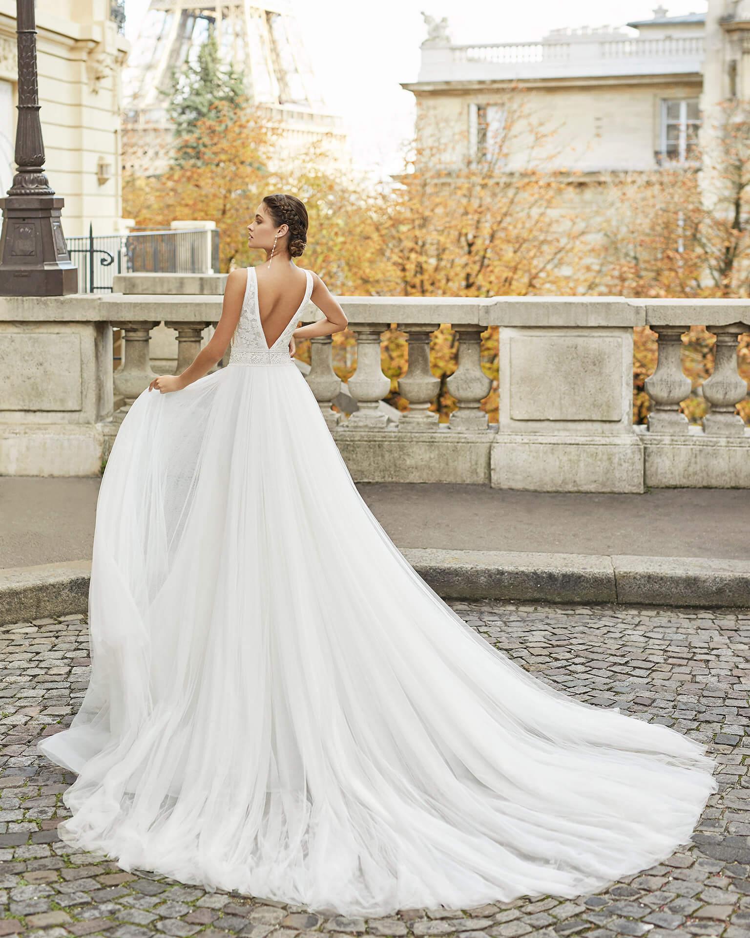 Braut in Brautkleid A-Linie Satin mit Träger ärmellos angewinkelter Arm Rückenansicht auf einer Brücke