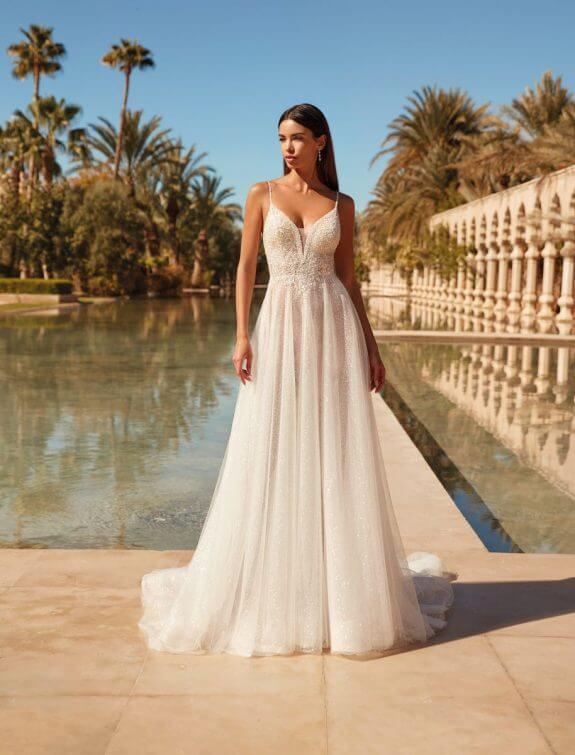 Braut in A-Linien Brautkleid mit schmalem Träger vor Wasser in Sonne im Palast Hof