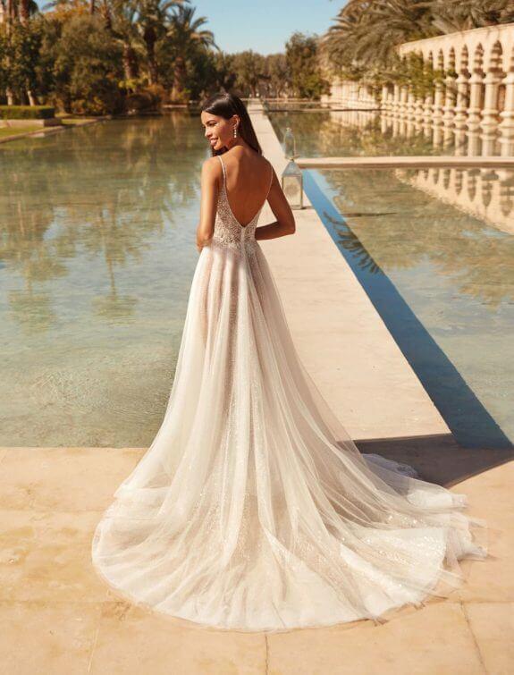 Lächelnde schwarzhaarige Braut in Brautkleid A-Linie mit schmalem Träger mit Schulterblick vor Wasser im Palast Garten