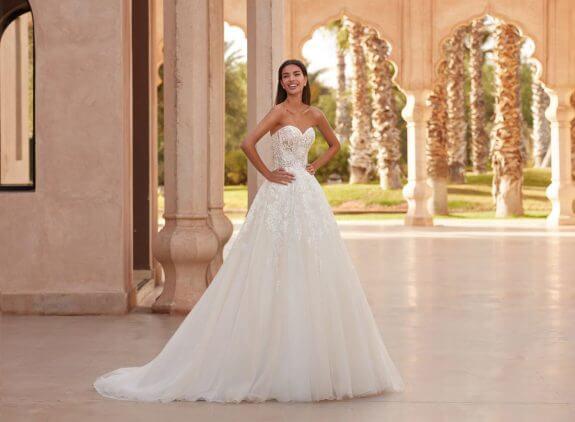 Schwarzhaarige Braut in Brautkleid A-Linie ärmellos mit Armen an der Hüfte im Schatten im Innenhof eines Palasts