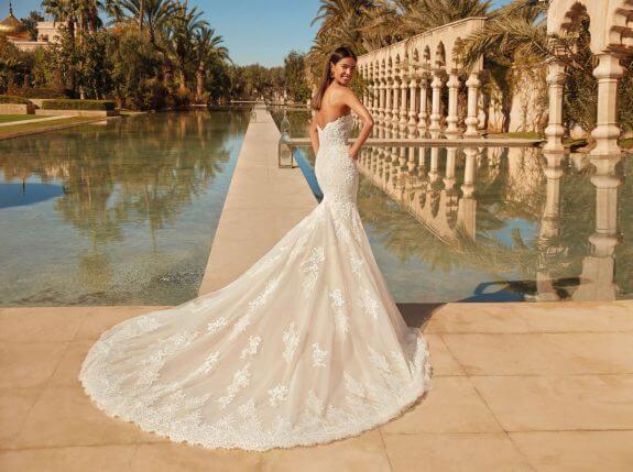 Schwarzhaarige Braut in trägerlosem Meerjungfrauen Brautkleid in Garten vom Palast mit Armen an der Hüfte in Rückenansicht