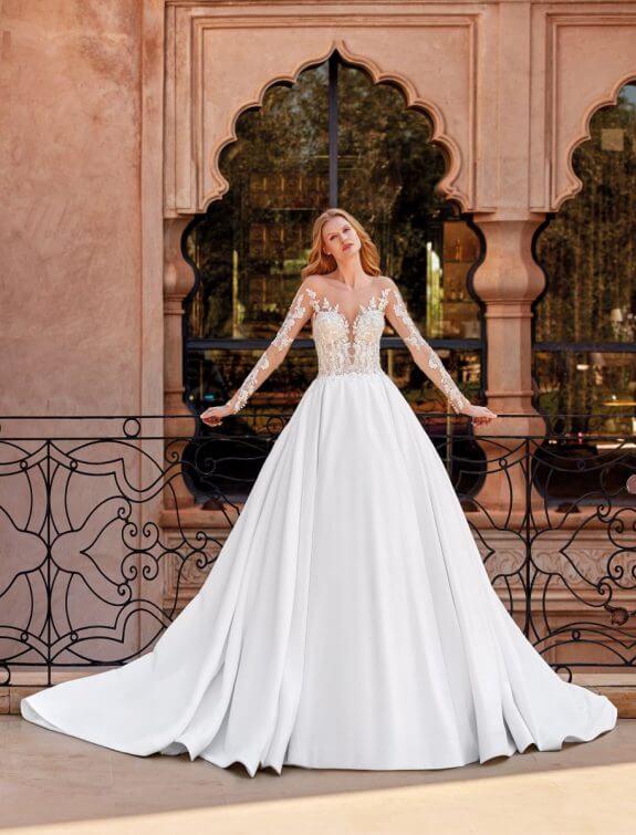 Blonde Braut in Brautkleid Prinzessin in Palast stützt sich beidhändig an Geländer mit und Blumenmuster am Arm und Rücken