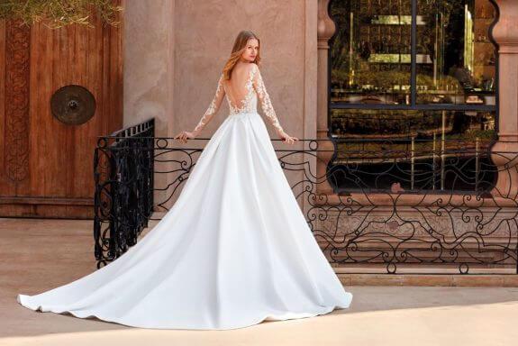 Blonde Braut in Brautkleid Prinzessin in Palast stützt sich an Geländer mit Schulterblick und Blumenmuster am Arm und Rücken