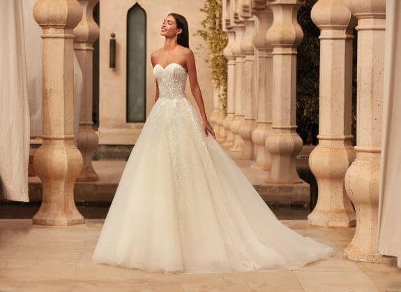 Lächelnde schwarzhaarige Braut in Brautkleid Prinzessin trägerlos in Palast Innenhof neben Säulen mit geschlossenen Augen