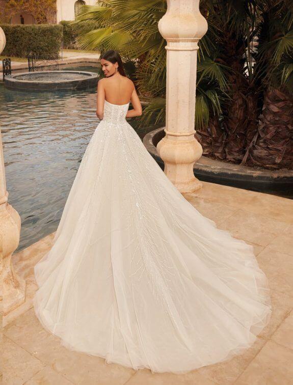 Schwarzhaarige Braut in Brautkleid Prinzessin trägerlos in Palast Innenhof neben Wasser Rückenansicht mit Blick über Schulter