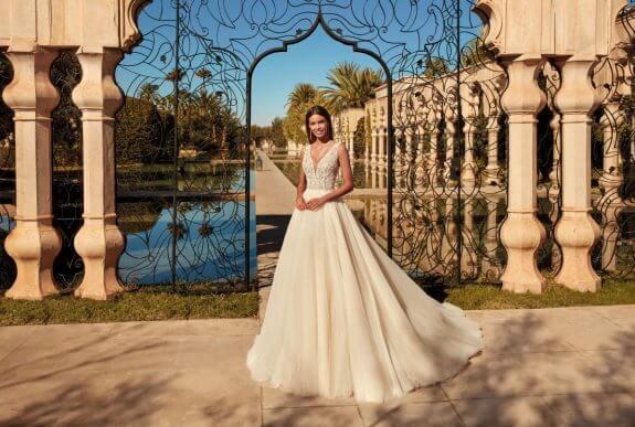 Lächelnde schwarzhaarige Braut in Brautkleid Prinzessin mit schmalem Trägersteht vor geöffnetem Tor neben Säulen