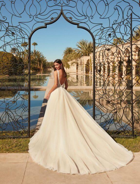 Lächelnde schwarzhaarige Braut in A-Linien-Brautkleid mit schmalem Träger steht vor geöffnetem Tor mit Schuilterblick