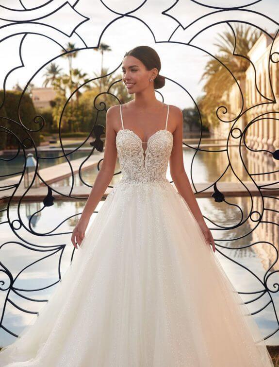 Schwarzhaarige Braut in Brautkleid A-Linie mit schmalem Träger vor einem Eingangstor mit Wasser im Hintergrund