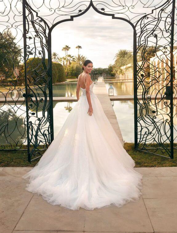 Schwarzhaarige lächelnde Braut in Brautkleid A-Linie mit schmalem Träger mit Schulterblick vor offenem Eingang eines Tors mit Wasser im Hintergrund