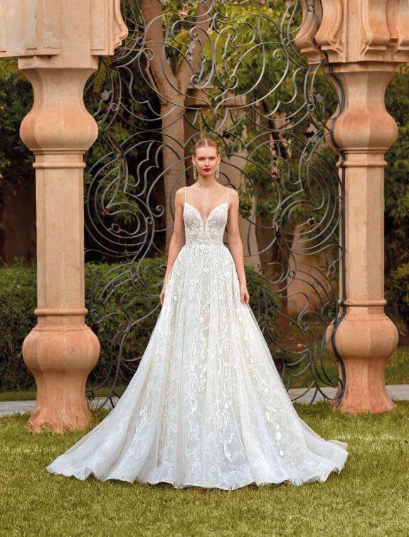 Blonde Braut in Brautkleid A-Linie mit schmalen Träger ärmellos in Garten von Palast