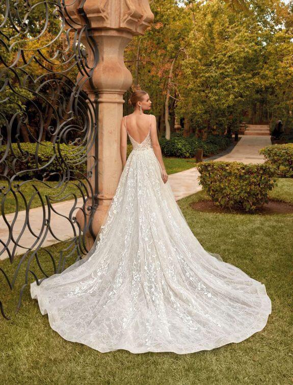 Blonde Braut in Brautkleid A-Linie mit schmalem Träger in Garten von Palast, angelehnt an eine Säule Schulterblick Rückenansicht