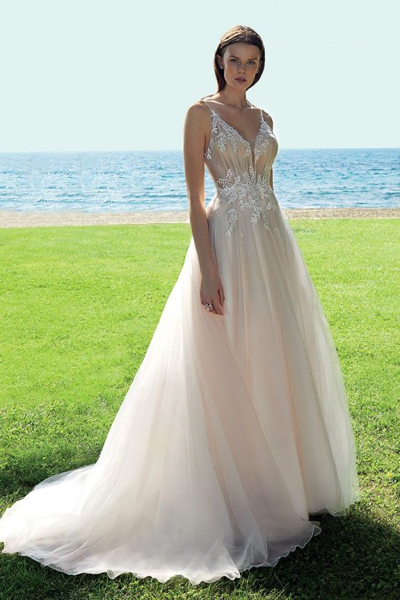 Braut in Brautkleid A-Linie auf Rasen vor einem Meer