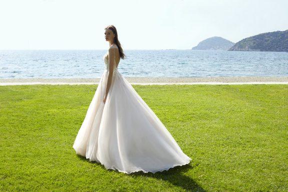 Braut in Brautkleid A-Linie auf Rasen vor einem Meer Seitenansicht