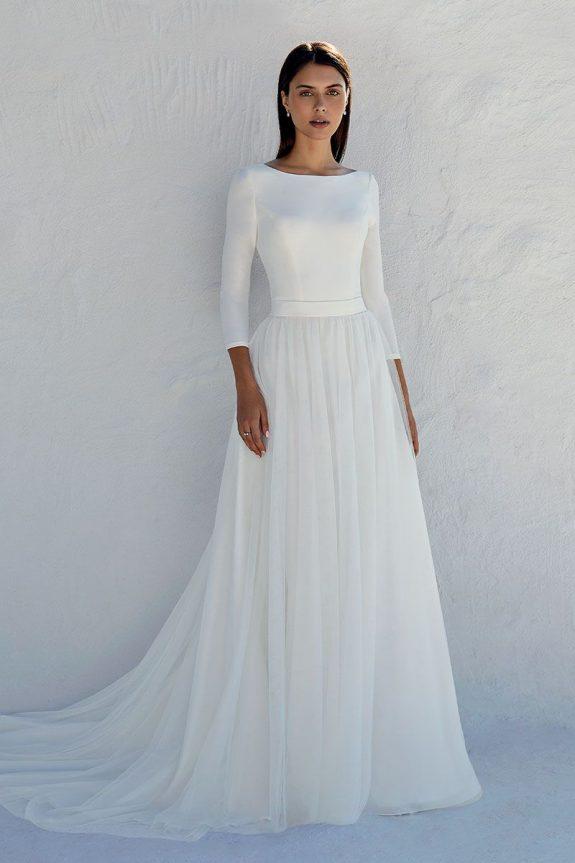 Schwarzhaarige Braut in A-Linien Brautkleid vor weißer Mauer in Schatten