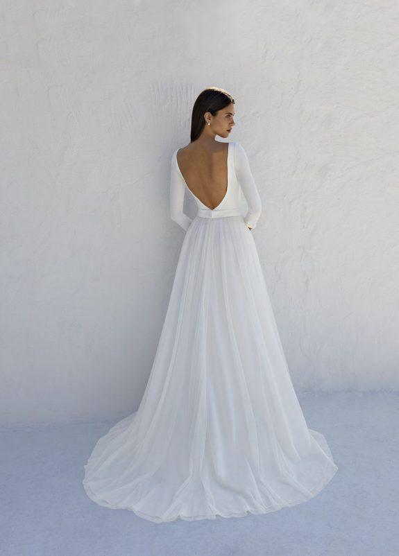 Schwarzhaarige Braut in Brautkleid A-Linie vor weißer Mauer in Schatten Rückenansicht V-Ausschnitt