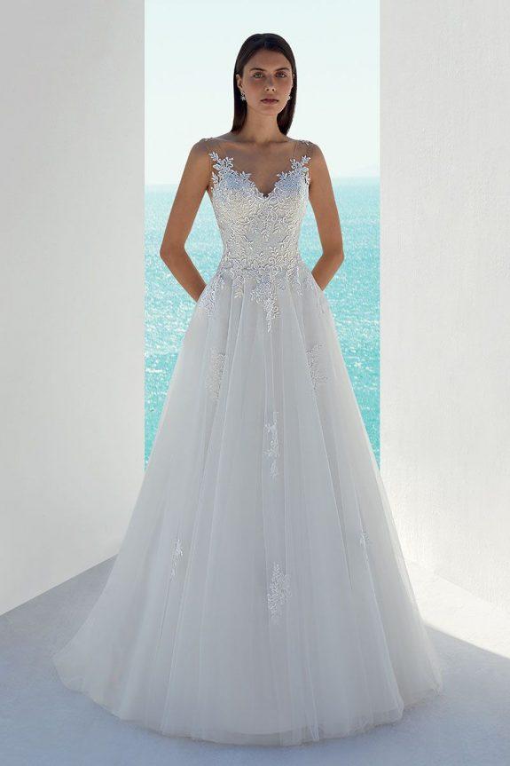Schwarzhaarige Braut in Brautkleid A-Linie zwischen weißen Mauern mit Meer im Hintergrund