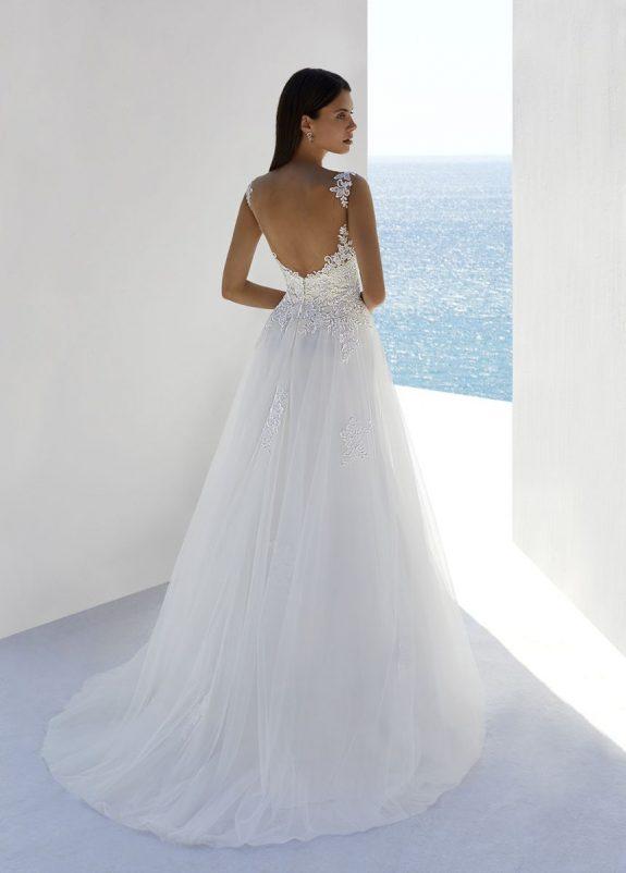 Schwarzhaarige Braut in Brautkleid A-Linie zwischen weißen Mauern mit Meer im Hintergrund Rückenansicht