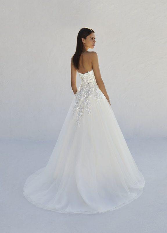 Braut in Brautkleid A-Linie vor weißer Mauer Rückenansicht mit Blick über die Schulter