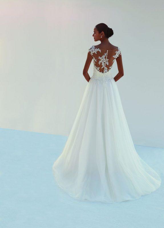 Braut in Brautkleid A-Linie vor weißer Mauer Rückenansicht