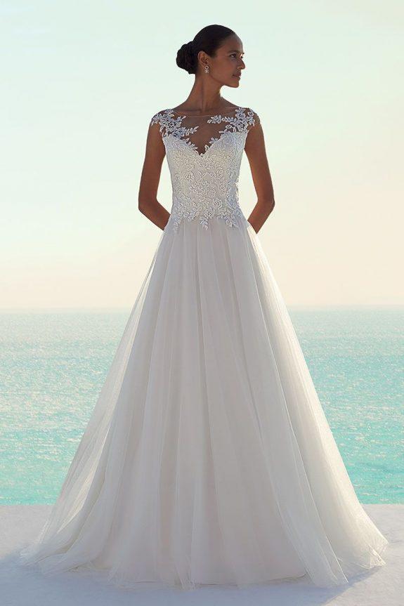 Braut in Brautkleid Fit & Flare vor einem Meer mit Armen hinter dem Rücken