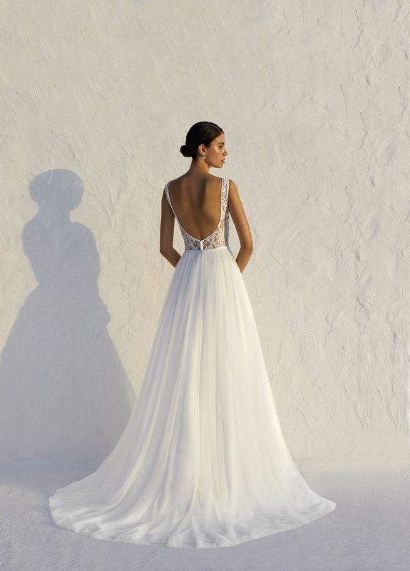 Braut in Brautkleid Fit & Flare vor weißer Mauer Rückenansicht in Sonne