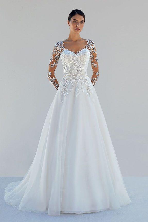Schwarzhaarige Braut in A-Linien Hochzeitskleid vor weißer Mauer in Schatten mit Blumenmuster am Ärmel