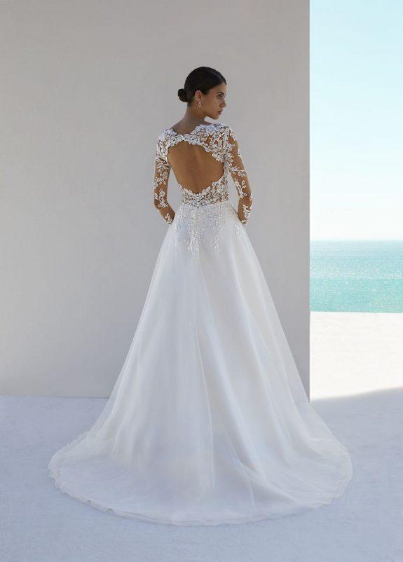 Schwarzhaarige Braut in A-Linien Brautkleid vor weißer Mauer im Schatten Rückenansicht mit Blumenmuster am Oberkörper mit Meer im Hintergrund
