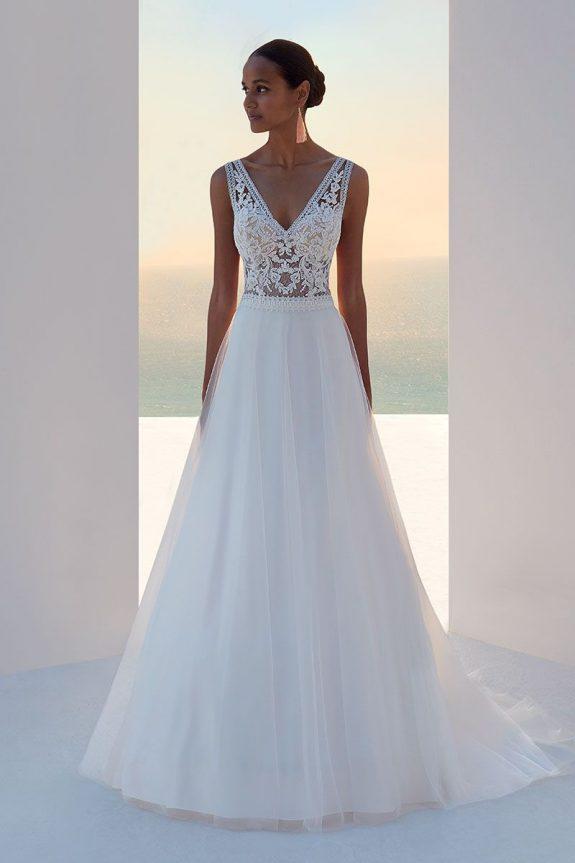 Schwarzhaarige Braut in Brautkleid A-Linie zwischen weißer Mauer in Schatten mit Meer & Himmel im Hintergrund