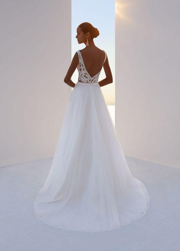 Schwarzhaarige Braut in Brautkleid A-Linie zwischen weißer Mauer in Schatten mit Meer & Himmel im Hintergrund Rückenansicht