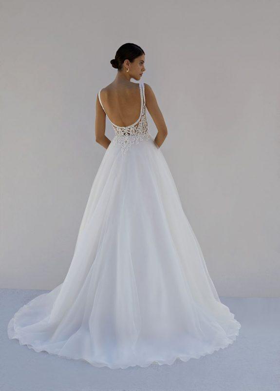 Schwarzhaarige Braut in Brautkleid A-Linie vor weißer Mauer in Schatten Rückenansicht rückenfrei