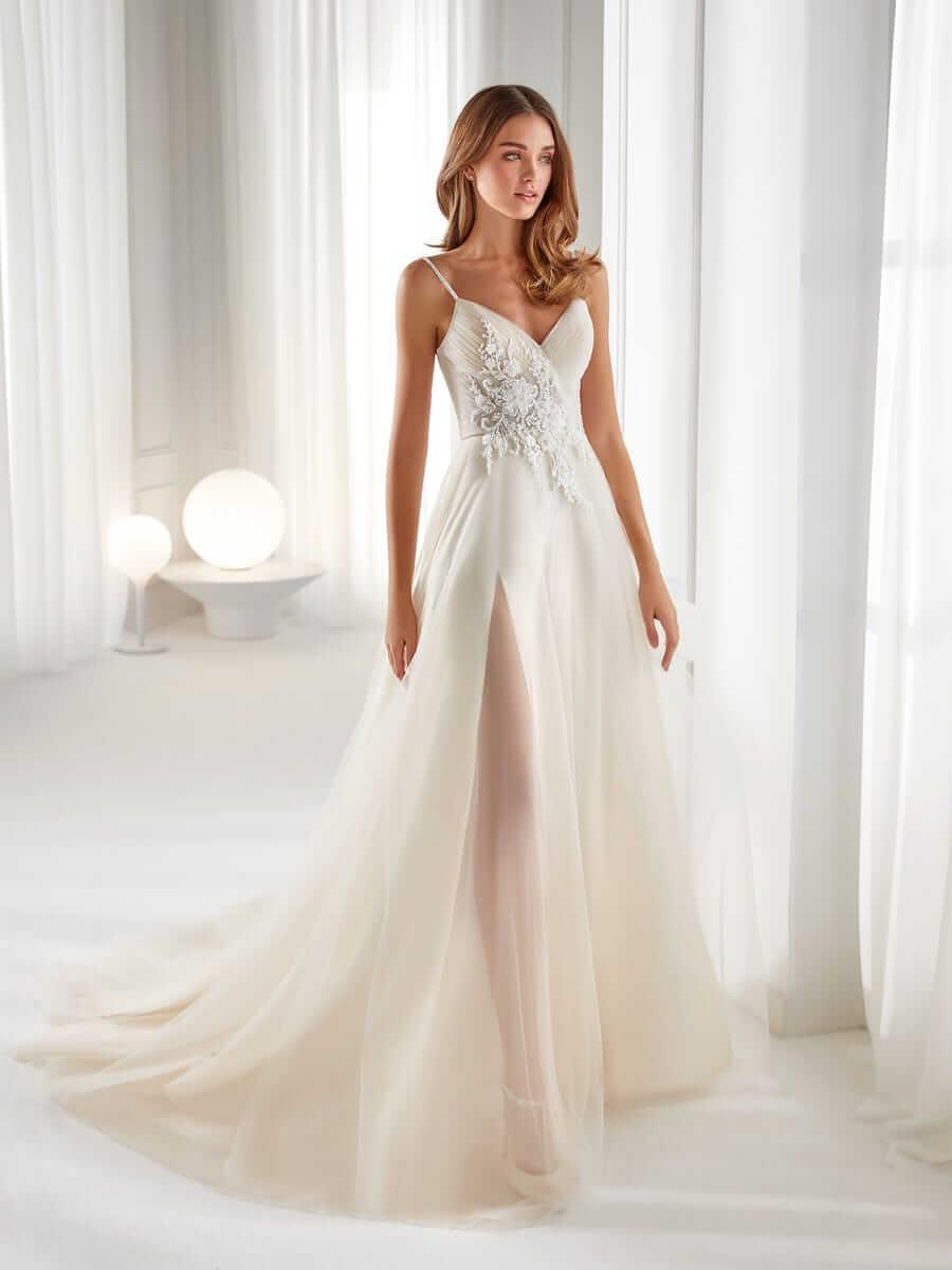 Blonde Braut mit A-Linien-Brautkleid, durchsichtig entlang der Beine und schmalem Träger in weißer Wohnung mit Beleuchtung