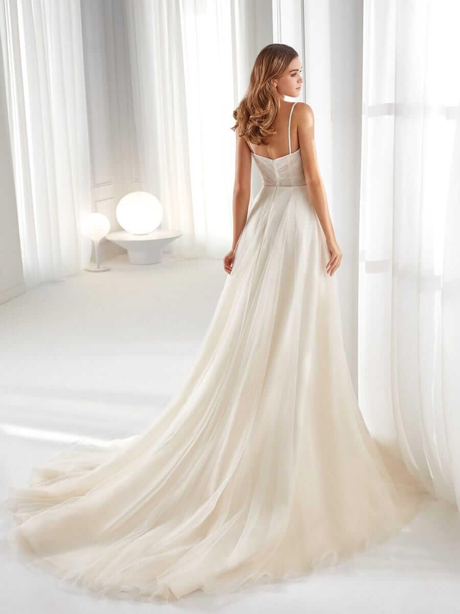 Brünette Braut mit A-Linien-Brautkleid und schmalem Träger in weißer Wohnung mit Beleuchtung in Rückenansicht