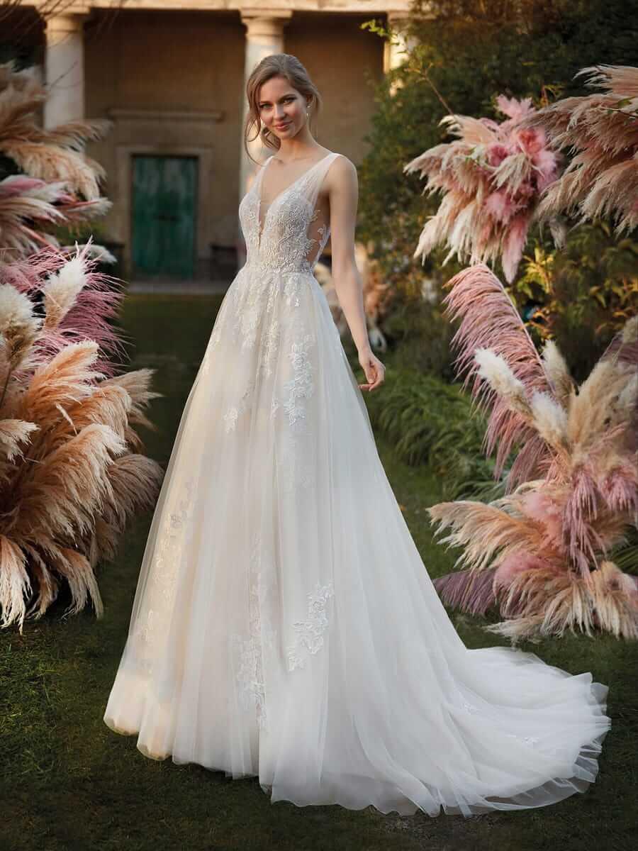 Brünette Braut in A-Linien-Brautkleid mit Träger neben Pampasgras in einem Garten im Schatten