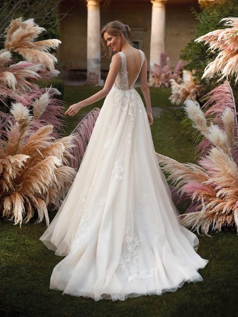 Lächelnde brünette Braut in A-Linien-Brautkleid berührt Pampasgras in Garten in Rückenansicht
