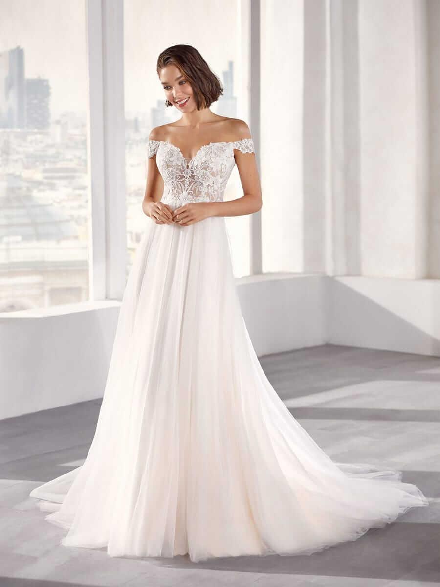 Lächelnde brünette Frau in A-Linien-Brautkleid mit Carmen Träger in weißem, hellen Raum vor großem Fenster