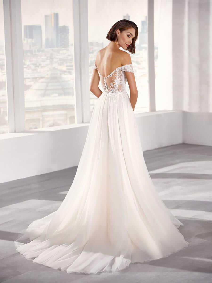 Brünette Braut in Brautkleid A-Linie mit Carmen Träger Rückenansicht Schulterblick in hellem, weißen Raum vor großem Fenster
